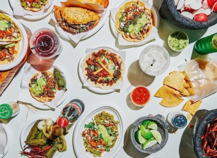 Overhead shot of a table with many plates of tacos and other dishes, drinks, etc.